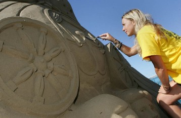 Sand sculptor, Nicola Wood, puts the finishing touches to her four meter high creation: ' Cinderella ' on the sea front at Weston-Super-Mare, Somerset.